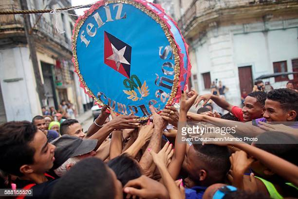 Cubans touch a candyfilled pinata that reads 'Feliz Cumpleanos' and bears the military symbol of comandante en jefe or commanderinchief during a...