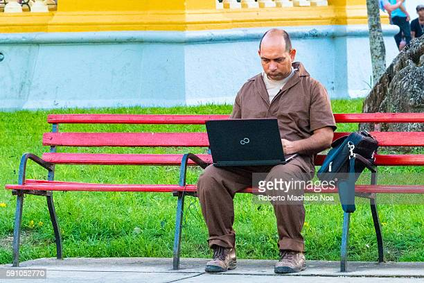 Cubans using wifi in open areas Middle age man sitting at the park using his laptop with the recently installed WiFi