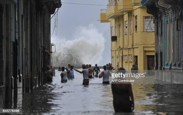 Cubans wade through a flooded street in Havana, on September 10, 2017. Deadly Hurricane Irma battered central Cuba on Saturday, knocking down power...