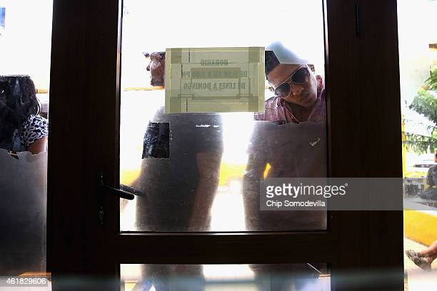 Cubans wait outside a Cubacel mobile phone shop for their turn to enter the shop and add value to their accounts at Jose Marti International Airport...
