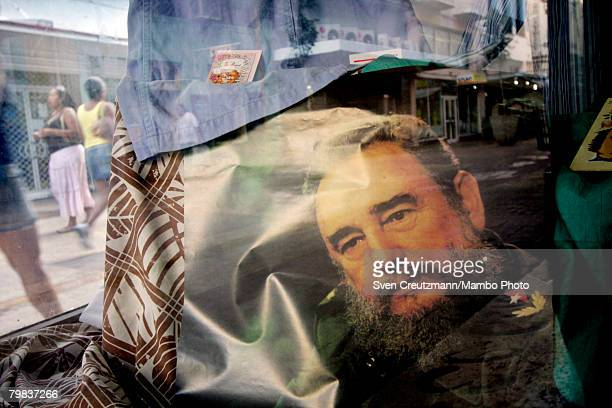 Cubans walk by a shop displaying a photo of Fidel Castro in the window after the official communist party newspaper Granma published a statement by...