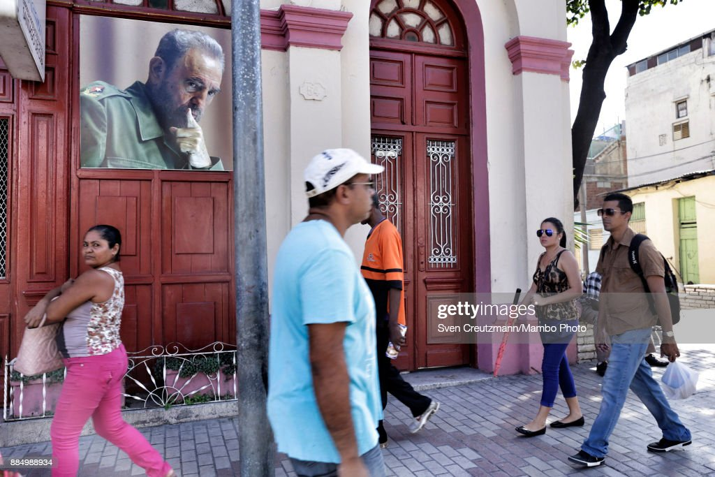 Cubans walk under a photo of late Cuban Revolution leader Fidel Castro as Cuba commemorates the first anniversary of Castro's funeral, on December 3, 2017 in Santiago de Cuba. Castro died on November 25 2016 and was buried on December 4th, 2016 in Santiago de Cuba. Cuba will hold elections in February who will define the successor of Cubaâs President, Raul Castro.