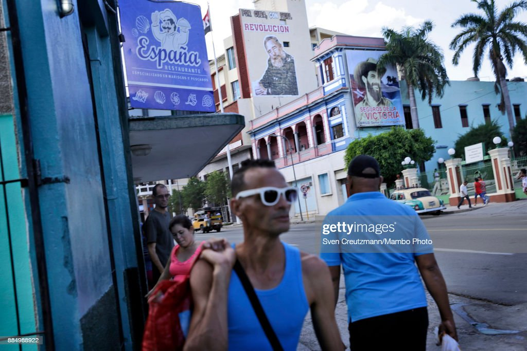Cubans walk under photos of late Cuban Revolution leader Fidel Castro (L) and Commander Camilo Cienfuegos (R) as Cuba commemorates the first anniversary of Castro's funeral, on December 3, 2017 in Santiago de Cuba. Castro died on November 25 2016 and was buried on December 4th, 2016 in Santiago de Cuba. Cuba will hold elections in February who will define the successor of Cubaâs President, Raul Castro.