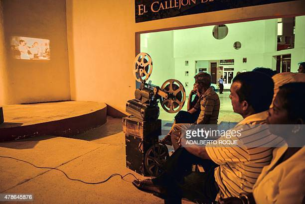"Cubans watch an old 16mm film screening in Casablanca bar --decorated as in US legend movie ""Casablanca""-- in Camaguey city, 600 km east of Havana,..."
