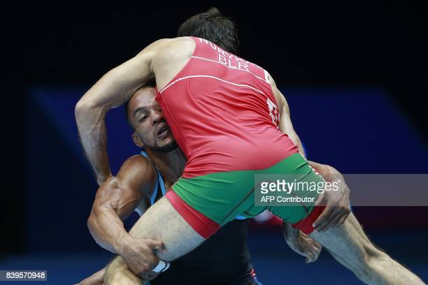 Cuba's Alejandro Valdes Tobier challenges Belarus' Azamat Nurykau during the men's freestyle wrestling 65kg category bronze medal playoffs at the...