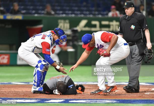 TOPSHOT Cuba's catcher Yosvani Alarcon and pitcher Vladimir Garcia check on Shawn Zarraga of the Netherlands after he was hit by a pitch in the top...