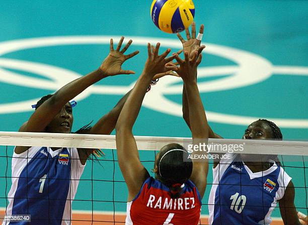 Cuba's Daimi Ramirez Echevarria vies for the ball with Venuezela's Yessica Paz Hidalgo and Desiree Glod during their women's preliminary volleyball...