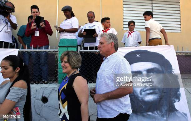 Cuba's First VicePresident Miguel DiazCanel and his wife Lis Cuesta stand next to an image of revolutionary leader Ernesto 'Che' Guevara as they...