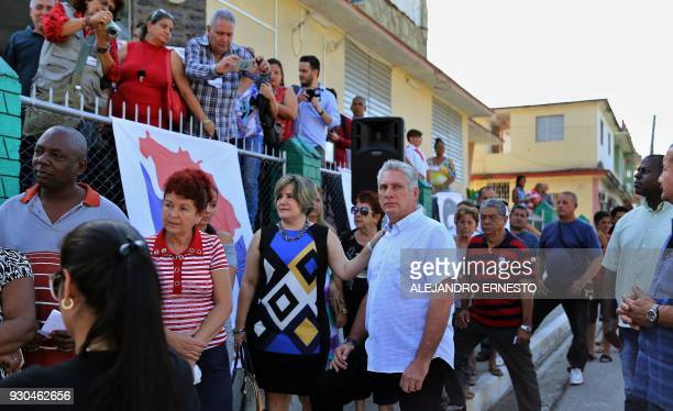 Cuba's First VicePresident Miguel DiazCanel and his wife Lis Cuesta queue at a polling station in Santa Clara Cuba during an election to ratify a new...