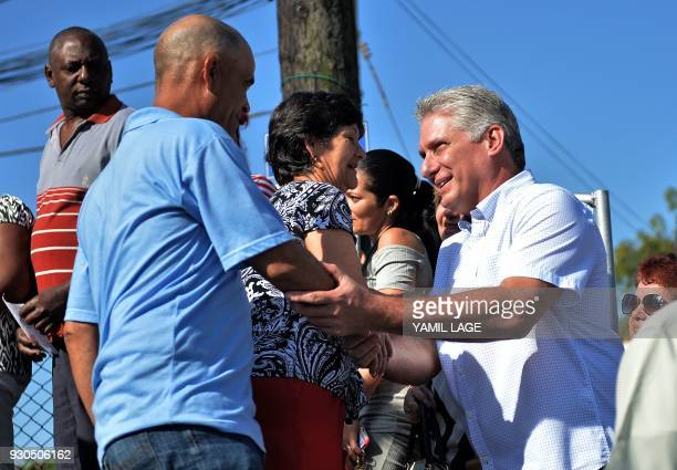 Cuba's First VicePresident Miguel DiazCanel greets people as he arrives at a polling station in Santa Clara Cuba during an election to ratify a new...