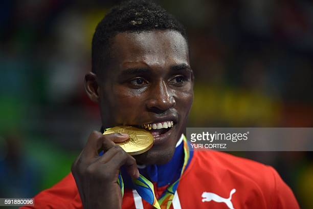 Cuba's Julio Cesar La Cruz poses on the podium with a gold medal after winning the Men's Light Heavy Final Bout match at the Rio 2016 Olympic Games...