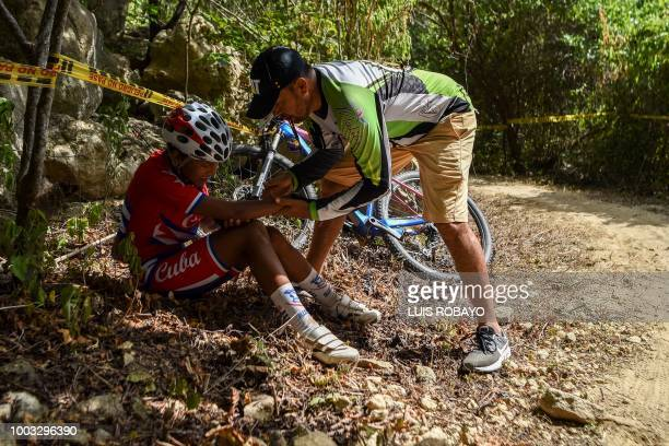 Cuba's Ludisneli Fleitas is assisted after falling during the Women's Mountain Bike Cross Country finals event of the cyclying competition of the...