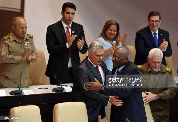 Cuba's new President Miguel DiazCanel is congratulated by First VicePresident Salvador Valdez Mesa as VicePresident Ramiro Valdez Menendez stands...
