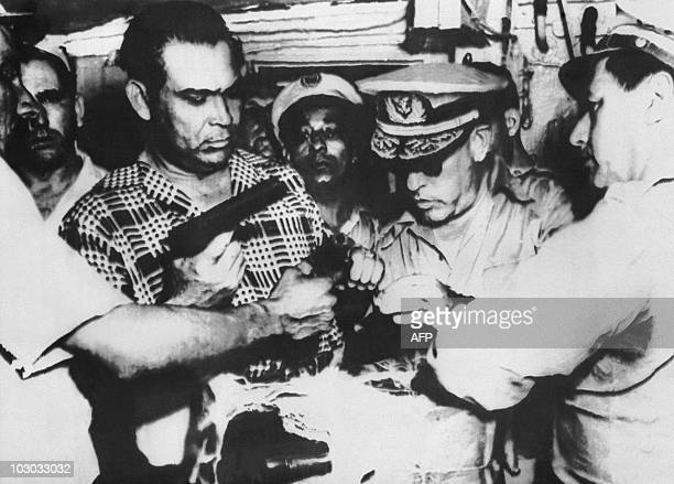 Cuba's President Fulgencio Batista inspects some of the arms and ammunition seized in Havana in connection with an intended Cuban revolt lead by...