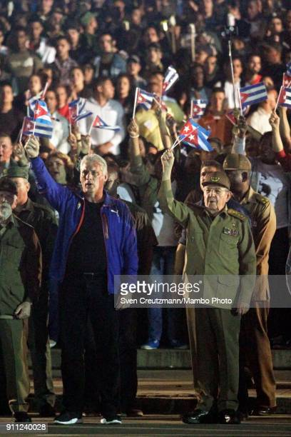 Cuba's President Raul Castro and First Vice President Miguel Diaz Canel wave with Cuban flags as singing the national anthem prior to leading a march...