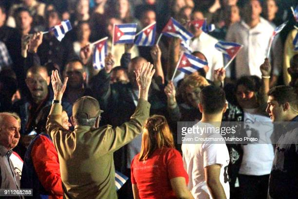 Cuba's President Raul Castro raises his arms as he greets prior to leading a march as Cuba celebrates the 165 anniversary of the birth of its...
