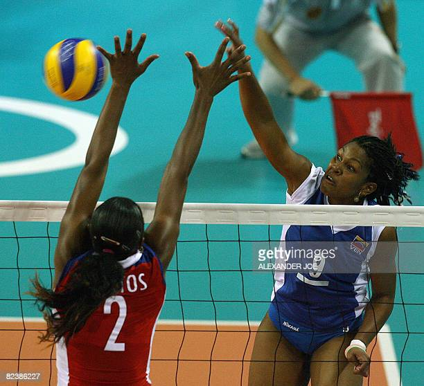 Cuba's Yanelys Santos Aantos tries to block a ball from Venuezela's Jayce Andrade Andrade during their women's preliminary volleyball match of the...