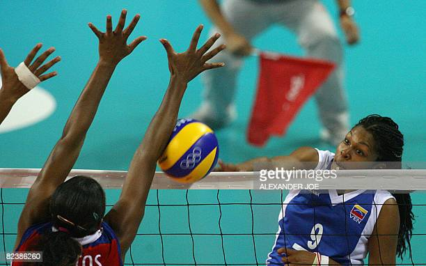 Cuba's Yanelys Santos Aantos tries to block the ball from a Venuezela's Jayce Andrade Andrade during their women's preliminary volleyball match of...