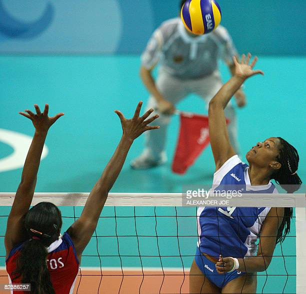 Cuba's Yanelys Santos Aantos tries to block the ball from Venuezela's Jayce Andrade Andrade during their women's preliminary volleyball match of the...