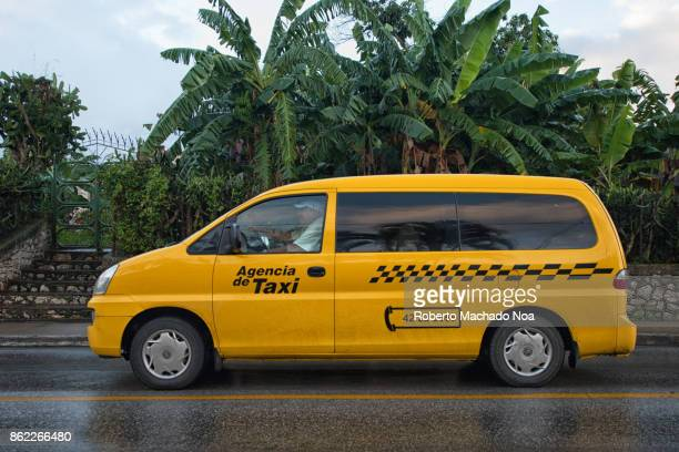 Cubataxi yellow and black van on the rainy Central Road
