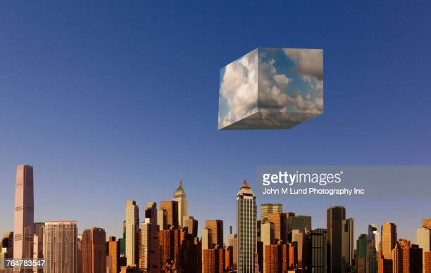 Cube of clouds floating over urban skyline