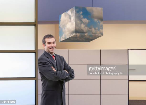 Cube of clouds hovering over Caucasian businessman