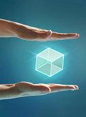 Cube of light floating between hands