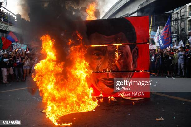 A cubic effigy painted with the face of President Rodrigo Duterte is set on fire by activists during a rally commemorating the 45th anniversary of...
