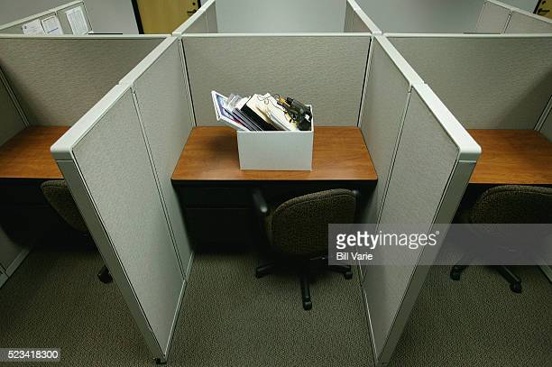 cubicle with box of personal belongings - downsizing unemployment stock pictures, royalty-free photos & images