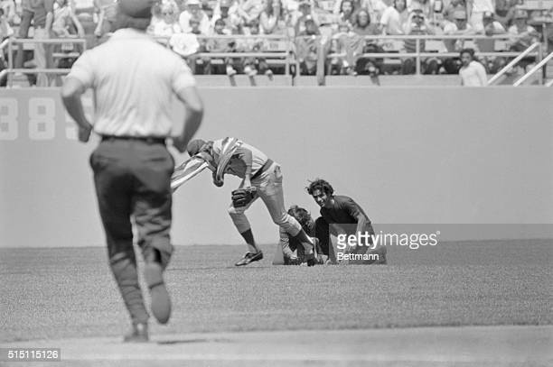 Cub's centerfielder Rick Monday clutching an American flag in one hand and his glove in the other races for the dugout after rescuing the flag from...