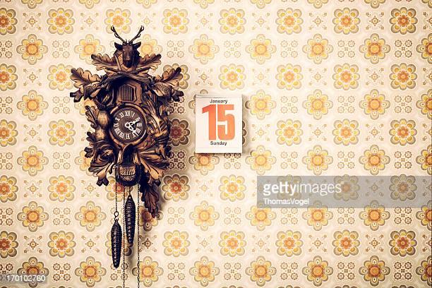 Kuckucksuhr und Kalender auf Retro Tapete
