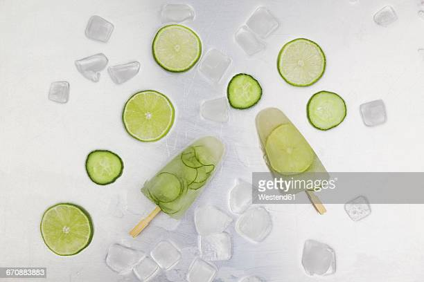 cucumber and lime ice lollies, ice cubes and slices of lime and cucumber on metal - stick stock-fotos und bilder