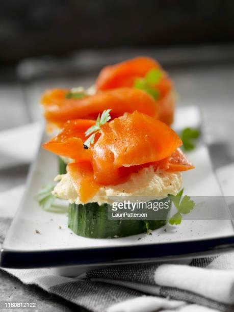 canape di cetriolo con salmone affumicato e hummus all'aglio arrosto - salmone affumicato foto e immagini stock