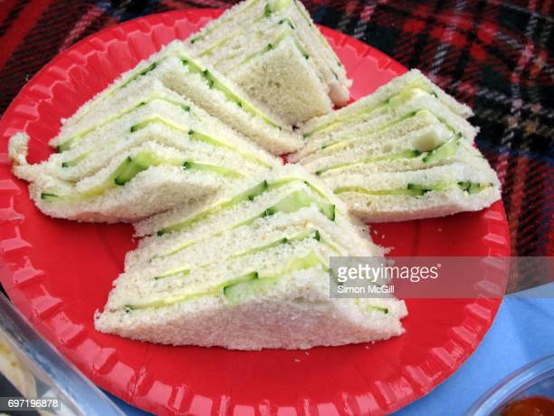Cucumber sandwiches on a red paper plate at a picnic
