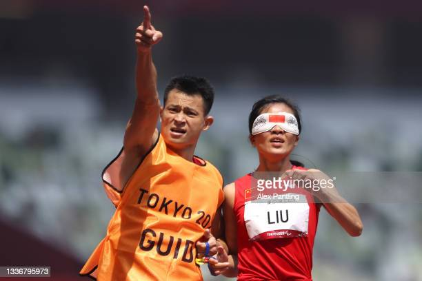 Cuiqing Liu of Team China celebrates with her guide after winning gold in the Women's 400m - T11 Final on day 4 of the Tokyo 2020 Paralympic Games at...