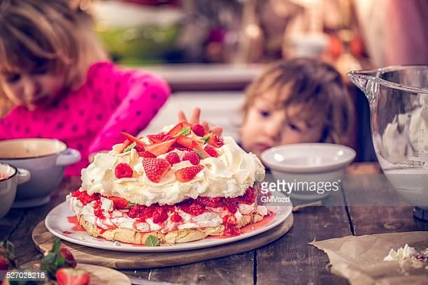 Cule enfants manger Berry Pavlova gâteau avec des fraises et framboises