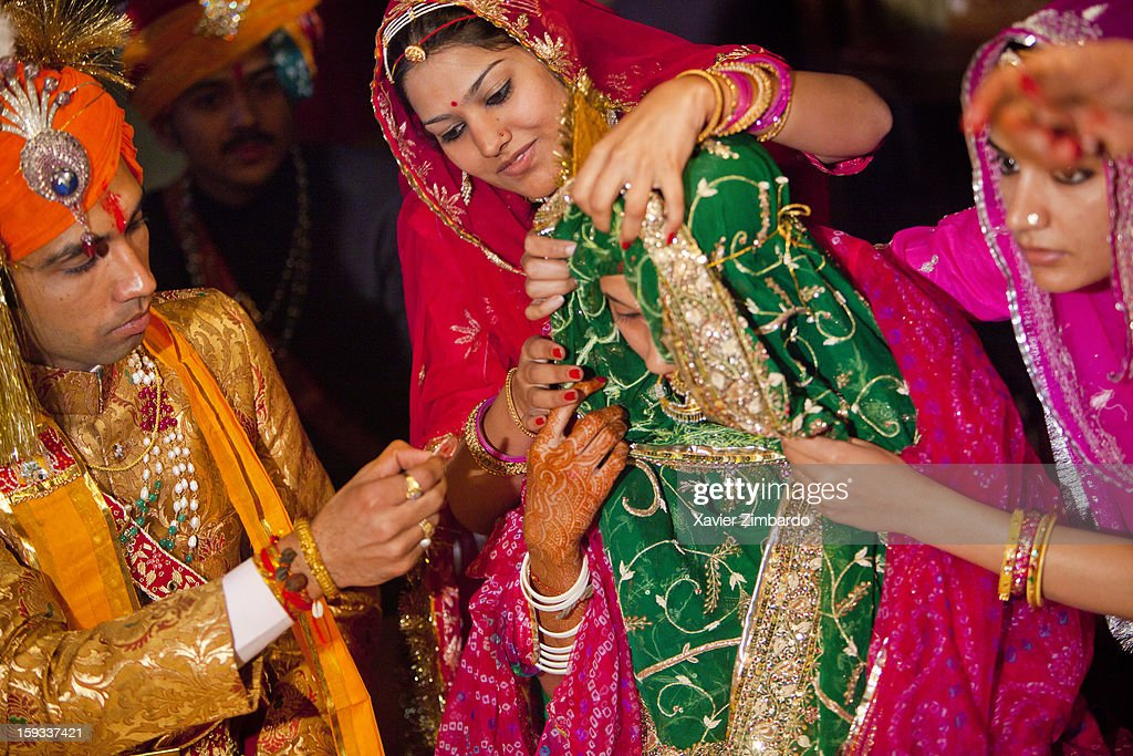 """Culmination of the ceremony, the bridegroom and the bride have accepted each other as husband and wife, and the groom applies vermilion """"sindoor"""" on the bride's forehead with a silver coin while the bride's friends are helping the bride to remove the upper part of her rajputi dress on February 19, 2011 in Barmer, Rajasthan, India."""