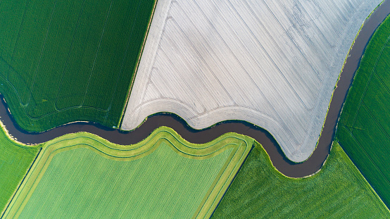 Cultivated land with natural stream seen from above - gettyimageskorea