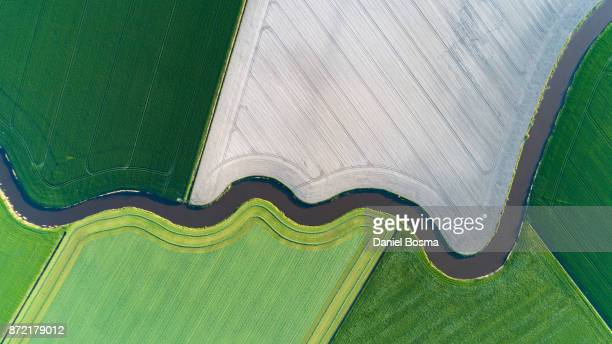 cultivated land with natural stream seen from above - luchtfoto stockfoto's en -beelden