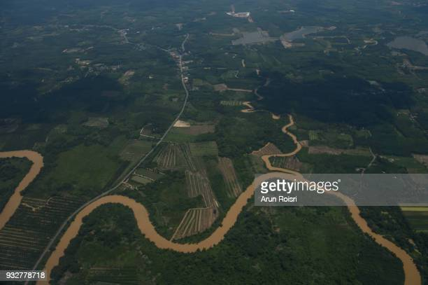 Cultivated landscape with roads and river, fields and trees in South Thailand.