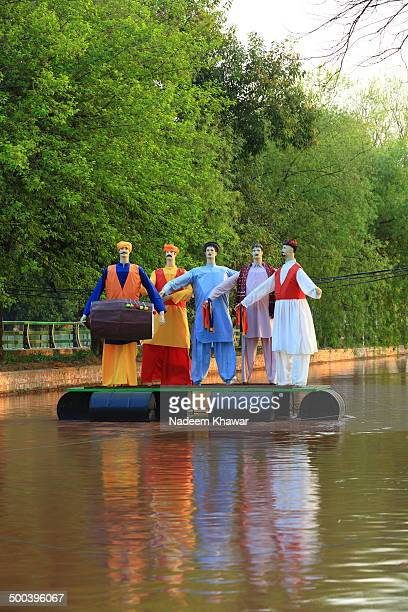 CONTENT] Cultural mannequins are standing on a platform in the running water of Lahore canal These statues was the part of spring festival for...