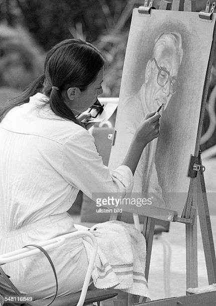 culture art painting young woman sits in front of an easel and paints a picture aged 20 to 30 years Spain Canary Islands Canaries Tenerife Puerto de...