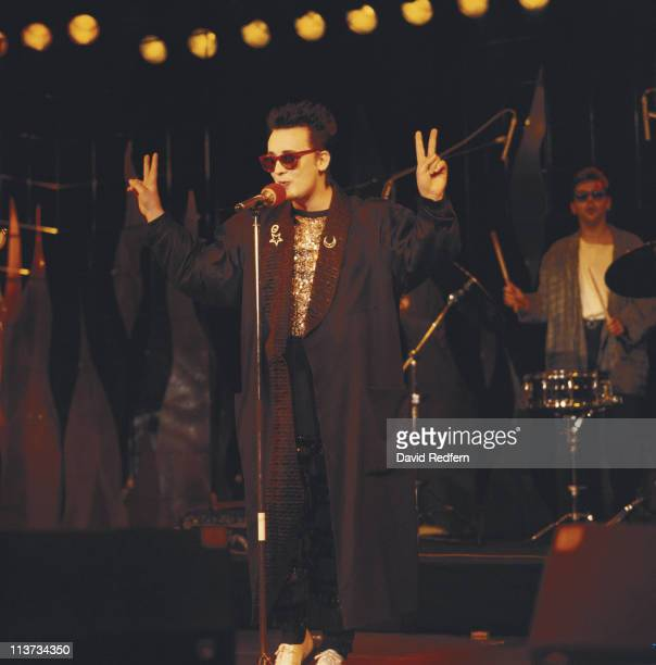 Culture Club singer Boy George holding up both hands held in the V sign peace symbol while singing into a microphone on stage during a live concert...