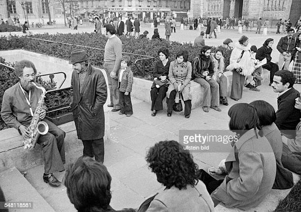 Culture, music, people sit on a public square and listen to a saxophonist, older man, aged 50 to 60 years, France, Paris -
