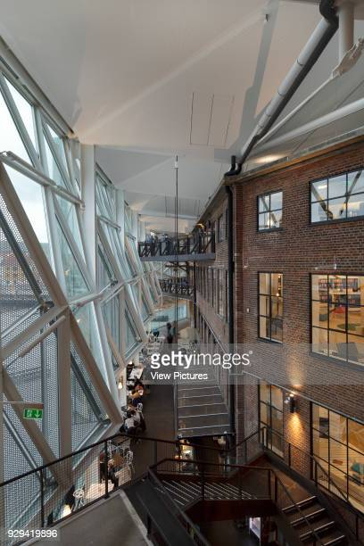Culture Yard , Helsingor, Denmark. Architect: AART Architects, 2010. Atrium, with original brick facade of shipbuilding yard on right, glass and...