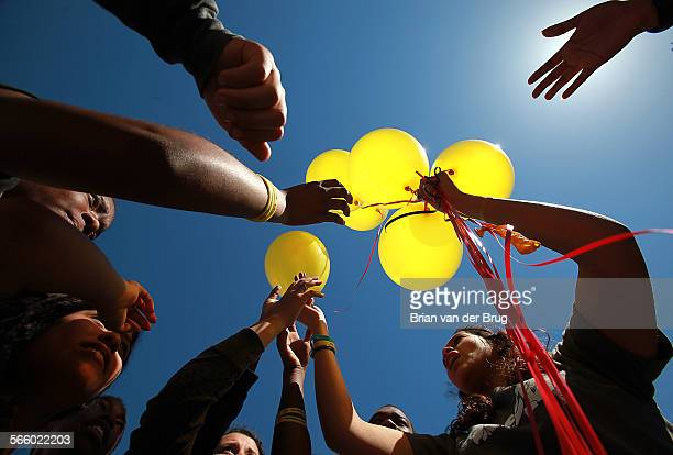Culver City High School student Natalie Argueta right passes out some of the nearly 300 balloons to be released during an assembly urging them to...