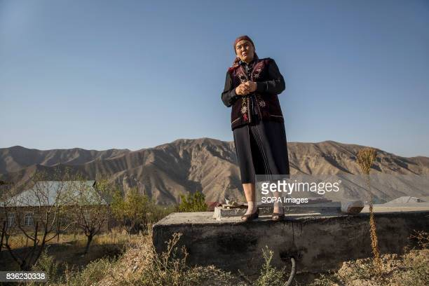 Cumagul Tolukbaeva who is an elementary school principal stands on top of a water reservoir used in Lyaily village where she lives with her family A...