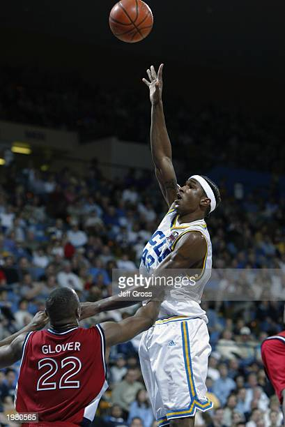 J Cummings of the University of California Los Angeles Bruins shoots over Anthony Glover of the St John's University Red Storm during the game at...