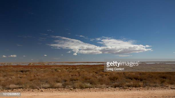 cumulus and altocumulus clouds over a lake in the australian outback beside a dirt road. - altocumulus stockfoto's en -beelden