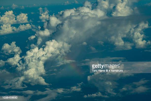 Cumulus clouds and rainbow on Pacific Ocean daytime aerial view from airplane